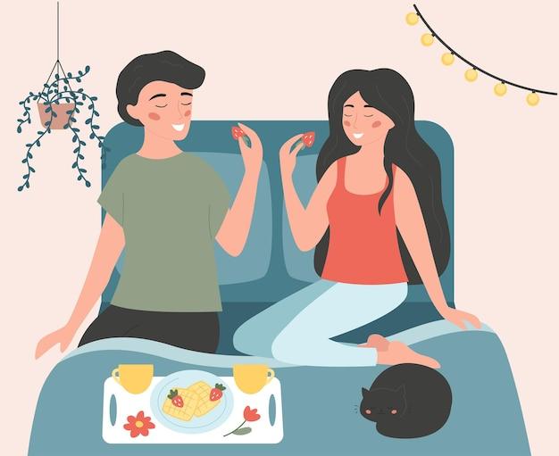 Nettes paar, das auf dem bett sitzt und frühstück isst.