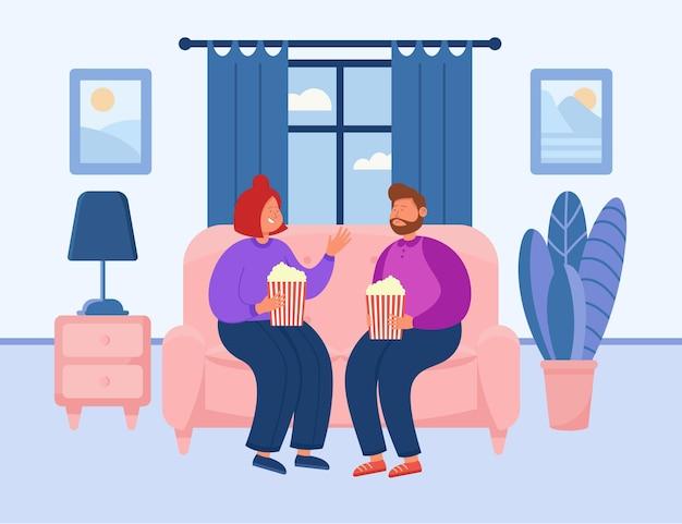 Nettes paar, das im gemütlichen haus einen film anschaut, während es popcorn isst