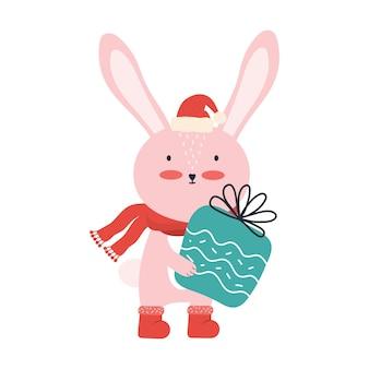 Nettes rosa babykaninchen in der weihnachtsmannmütze mit einer großen geschenkbox. lustiges karikaturtier isoliert