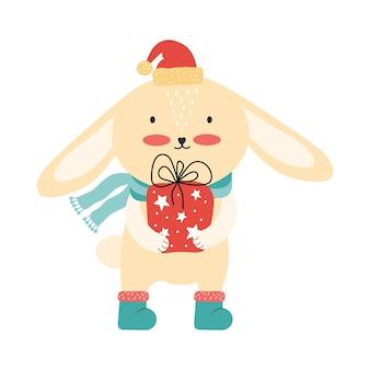 Nettes rosa babykaninchen in der weihnachtsmannmütze mit einer großen geschenkbox. lustiges weihnachtskarikaturtier isoliert
