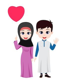 Nettes schönes arabisches kinderpaar, das steht und winkt und auf herzform mit traditionellem kleid lokalisiert zeigt