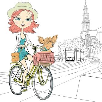 Nettes schönes modisches mädchen mit hund reitet ein fahrrad in amsterdam