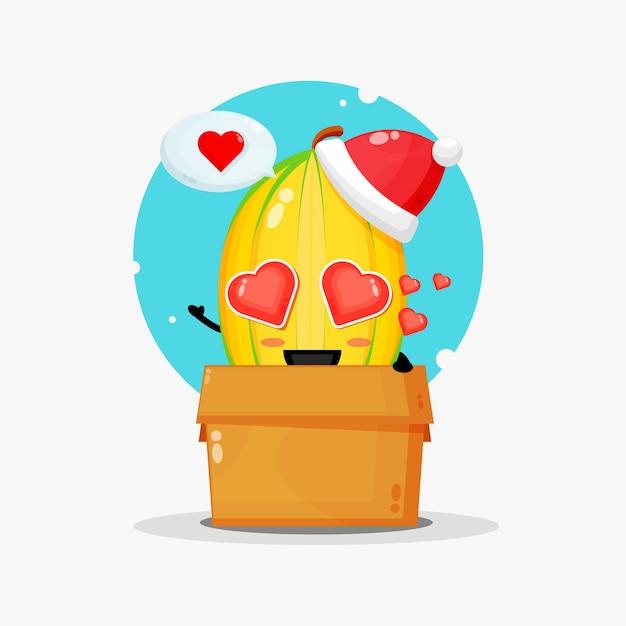 Nettes sternfruchtmaskottchen in einer schachtel, die eine weihnachtsmütze trägt