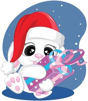 Nettes weihnachtskaninchen mit mit geschenk- und sankt-hut-frohen weihnachten und karikatur des neuen jahres