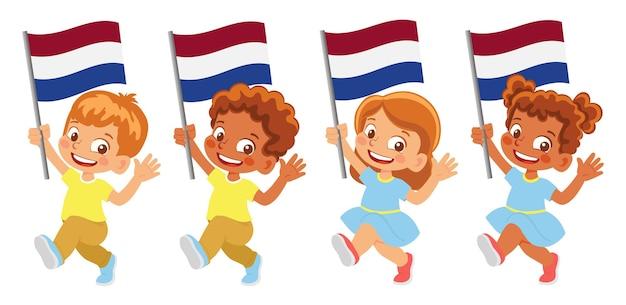 Niederländische flagge in der hand. kinder, die flagge halten. nationalflagge der niederlande