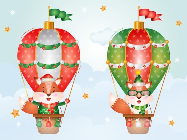 Niedliche fuchsweihnachtsfiguren auf heißluftballon mit einer weihnachtsmütze, einer jacke und einem schal