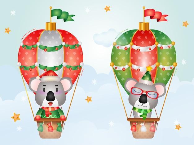 Niedliche koala-weihnachtsfiguren auf heißluftballon mit einer weihnachtsmütze, einer jacke und einem schal