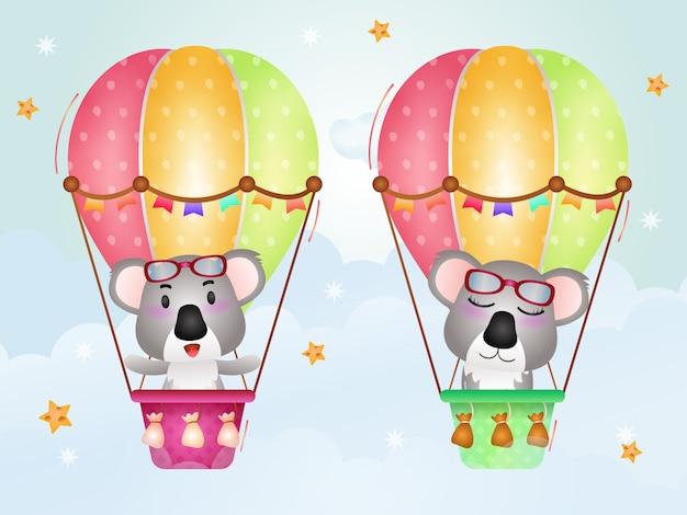Niedliche koalas auf heißluftballon