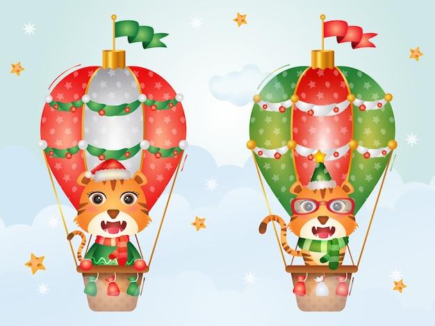 Niedliche tiger-weihnachtsfiguren auf heißluftballon mit einer weihnachtsmütze, einer jacke und einem schal