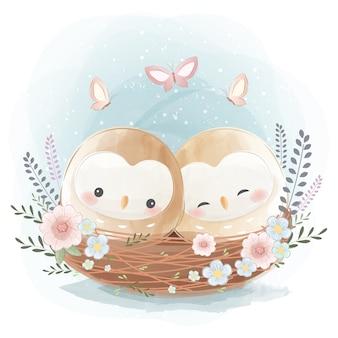 Niedliche zwei kleine eulen auf einem nest