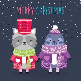 Niedlicher waschbär und mönch der feier der frohen weihnachten versiegeln mit strickjacken- und schalschneedekoration