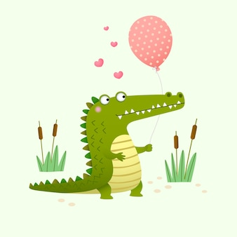 Niedliches krokodil, das einen ballon auf grünem hintergrund hält.