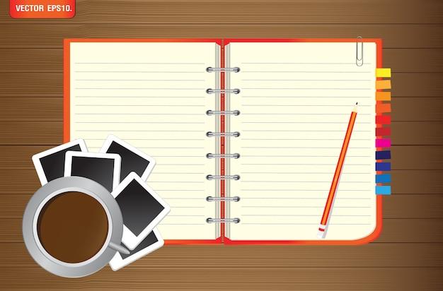 Notizbuch mit fotorahmen und kaffeetasse auf hölzernem hintergrund