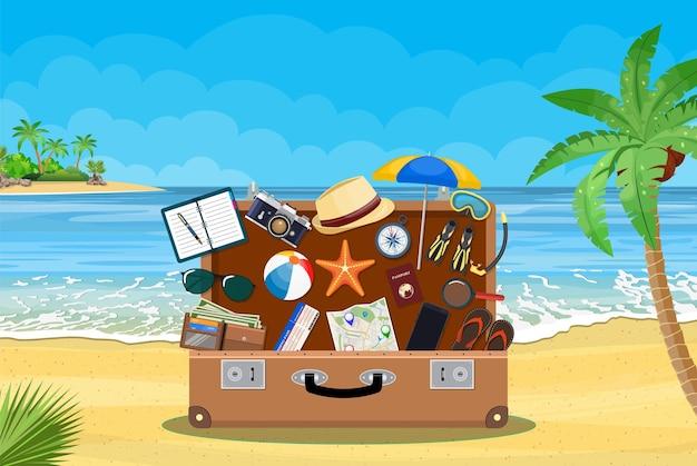 Offenes gepäck mit reisesymbolen und objekten auf tropischem hintergrund.