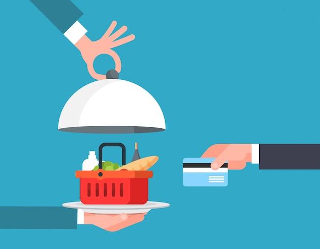 On-line-lebensmittelbestellungs-und zustelldienst-konzept-hand, die korb von lebensmittelgeschäft-produkten mit kreditkarte zahlt
