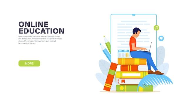 Online-bildung. junger mann, der mit laptop auf einem stapel bücher sitzt und entfernt online-kurs studiert.