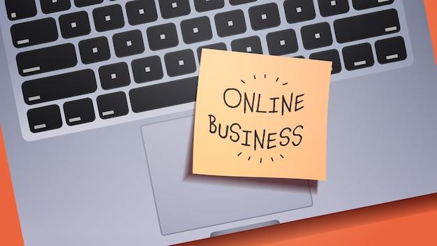 Online-business-llettering auf haftnotizpapier auf laptop-tastatur kreative idee konzept