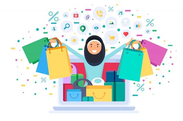 Online einkaufende muslimische frau hält taschen vom laptop