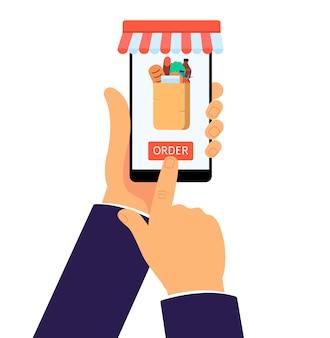 Online-lebensmittelgeschäft app auf dem handy. internetkauf von lebensmitteln in papiertüte, geschäftsmannhände, die ein smartphone halten und roten bestellknopf drücken - isolierte flache vektorillustration