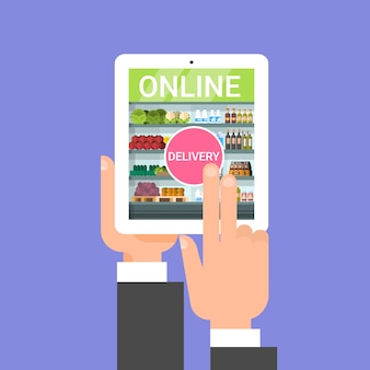 Online-lebensmittellieferung mit der hand, die lebensmittel mit digital-tablet-anwendung bestellt