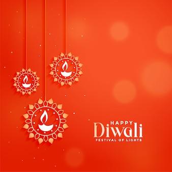 Orange diwali festivalkarte mit hängenden diya lampen