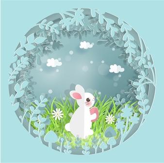 Ostern-Karte mit dem netten Kaninchen, das Ei im Wald hält