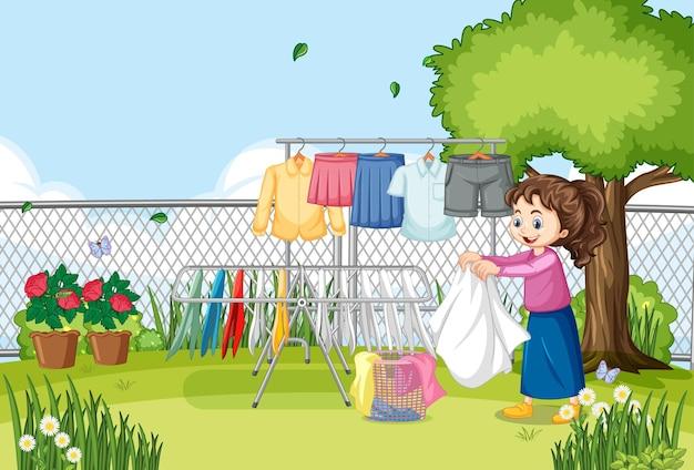 Outdoor-szene mit einem mädchen, das kleidung an wäscheleinen hängt