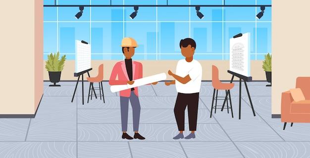 Paar architekten mit aufgerollten blaupausen diskutieren neue projektingenieure team bauindustrie konzept moderne zeichner studio interieur in voller länge horizontal