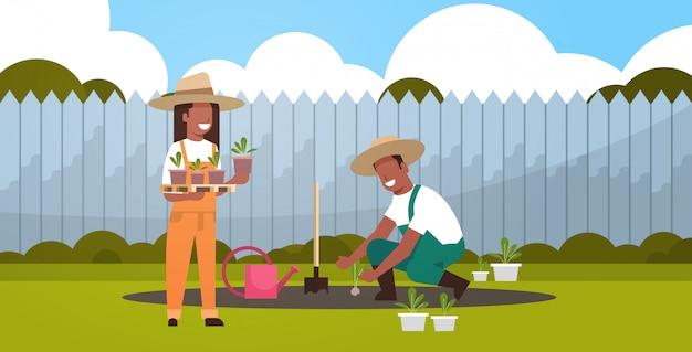 Paar bauern, die junge setzlinge pflanzen, pflanzen blumen und gemüse mann frau, die im garten öko-landwirtschaftskonzept hinterhof hintergrund in voller länge horizontal arbeitet