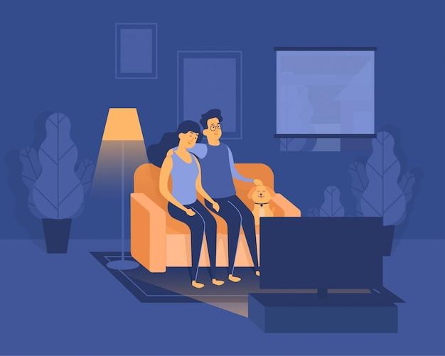 Paar bleiben zu hause und schauen nachts zusammen mit einem hund glücklich fern während der pandemie-quarantäne