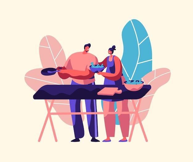 Paar, das frischen salat im freien kocht. ehemann und ehefrau bereiten gemeinsam das abendessen vor.