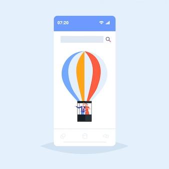 Paar, das im korb der heißluftballonfrau unter verwendung des tablet-mannes fliegt, der hand auf etwas romantisches datumserkundungskonzept-smartphone-bildschirm der mobilen app zeigt