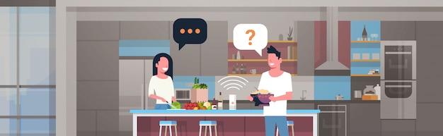 Paar, das intelligenten lautsprechermannfrau verwendet, die essen bereitet, das rezept spracherkennungskonzept moderne küche innen flaches horizontales porträt fragt