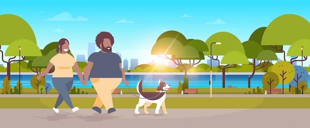 Paar, das mit husky-hundemannfrau geht, die spaß im freienstadt-stadtparkkonzept-sonnenuntergang hat