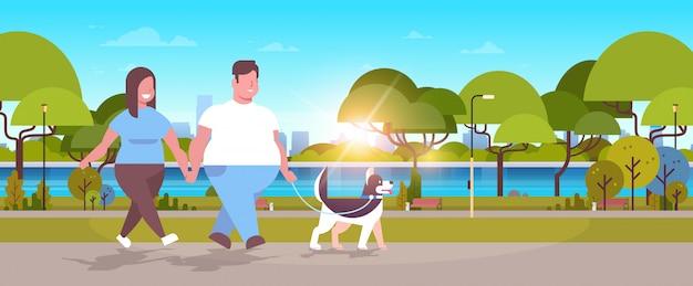 Paar, das mit husky-hundemannfrau geht, die spaß im stadtpark-fettleibigkeitskonzept der stadt im freien hat