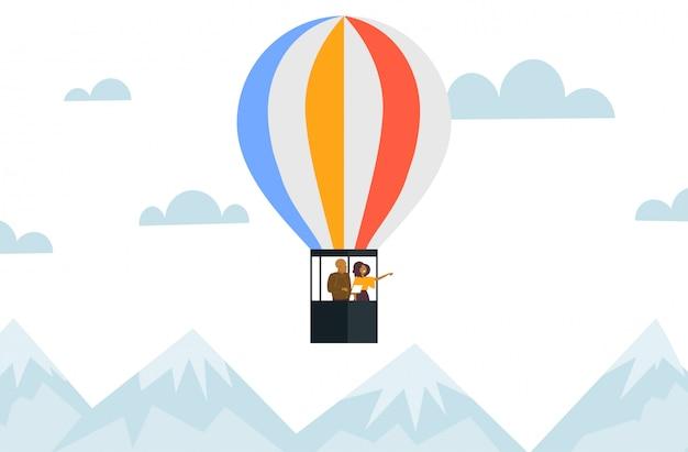 Paar fliegt im korb des heißluftballon-afroamerikanermannes unter verwendung der tablettfrau, die hand auf etwas romantisches datumskonzeptgebirgslandschaftshintergrund horizontal zeigt