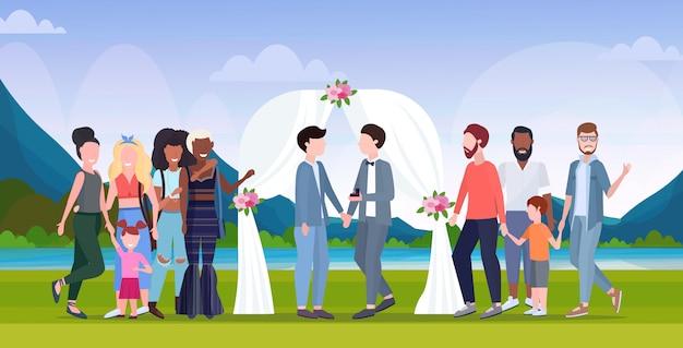Paar frisch verheiratete schwule, die hinter blumenbogen des gleichen geschlechts glücklich verheiratete homosexuelle familienhochzeit stehen, die konzeptlandschaftshintergrund in voller länge flach horizontal feiert