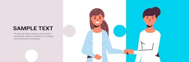 Paar geschäftsfrauen händeschütteln geschäftspartner händedruck während der besprechungsvereinbarung partnerschaftskonzept kolleginnen stehen zusammen flach porträt horizontale puzzleteile kopieren raum