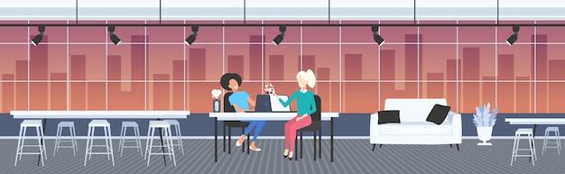 Paar geschäftsfrauen kollegen diskutieren während der kaffeepause mix race business frauen sitzen am arbeitsplatz kommunikationskonzept moderne büro innen nacht stadtbild in voller länge horizont