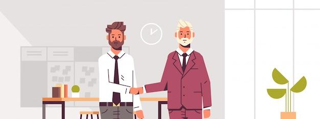 Paar geschäftsleute händeschütteln geschäftspartner händedruck während der besprechungsvereinbarung partnerkollegen stehen im modernen büro-interieur des co-working centers