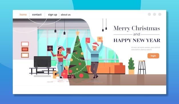 Paar hält geschenk geschenkboxen frohe weihnachten frohes neues jahr urlaubsfeier konzept mann frau trägt weihnachtsmützen moderne wohnzimmer innen landing page