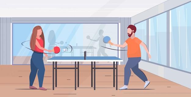 Paar hält schläger übergewichtige mann frau spielt tischtennis tischtennis gewichtsverlust konzept moderne turnhalle studio interieur flach in voller länge horizontal