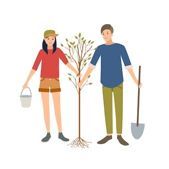 Paar junge fröhliche männliche und weibliche freiwillige oder ökologe, die zusammen baum im park pflanzen