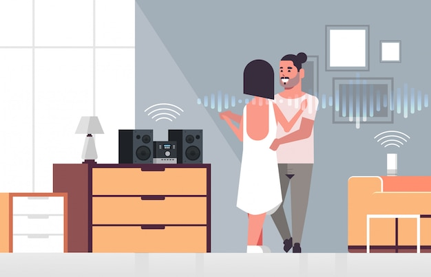 Paar mit hifi-stereoanlage, die über die spracherkennung mit intelligenten lautsprechern gesteuert wird