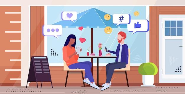 Paar mit online-mobile-app social-media-netzwerk chat-blase kommunikation digitale sucht konzept mix rasse mann frau sitzt am tisch straße café außenskizze in voller länge horizontal