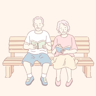 Paar mittleren alters, das bücher liest und auf parkbank sitzt