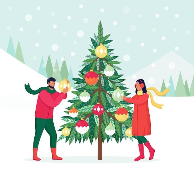 Paar schmückt weihnachtsbaum mit dekorationskugeln, girlande. familie, die sich auf die feier vorbereitet. frohe weihnachten und ein glückliches neues jahr. menschen feiern winterferien. mann hängt spielzeug an tanne