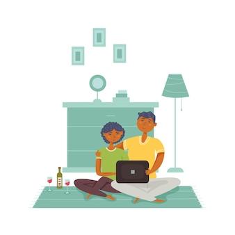 Paar sitzt auf dem boden und schaut nach einem laptop, der wein trinkt