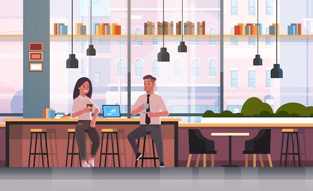 Paar sitzt auf stuhl am bartheke mit laptop-kaffeepause-geschäftsmannfrau, die cappuccino während des treffens des modernen café-innenraums trinkt