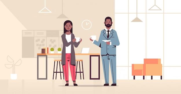 Paar trinkt cappuccino-geschäftsmannfrau, die während des treffens des kaffeepausenkonzepts des modernen büroinnenraums in voller länge horizontal diskutiert